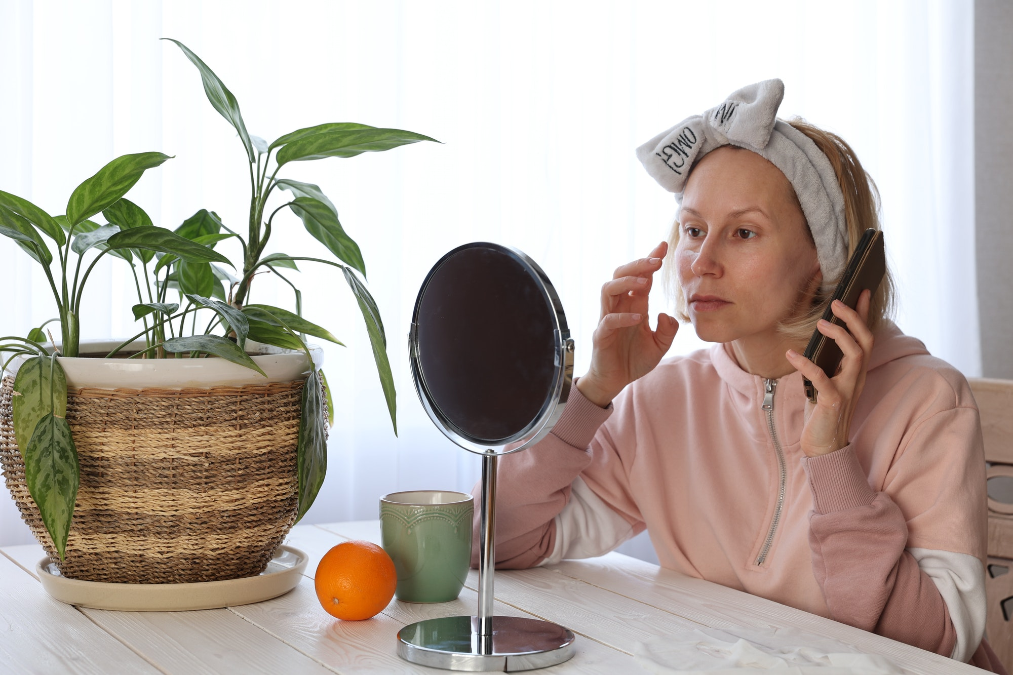 A woman does cosmetic procedures in front of a mirror